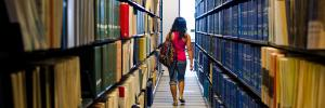 Student walking between rows of books in library
