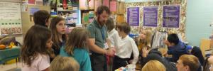 Photo of a student teacher working in a middle school art classroom with children.