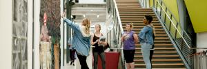 Image of students discussing a large piece of art hung in the Art and Visual Studies Building main lobby.