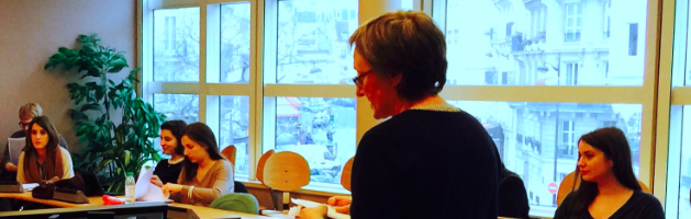 professor quanquin speaking to her class with the parisian urban landscape visible through the windows