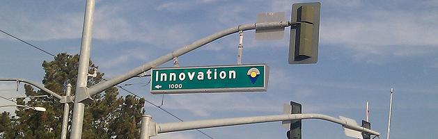 "street sign on stoplights at an intersection reading ""Innovation"""