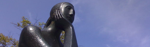 a statue of a person with her hand on her chin, thinking, with the blue sky behind her