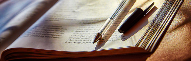 close up of an open booklet and uncapped pen on a table