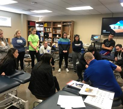 Students at UK CERH watch as Dr. Pat Kitzman assesses used medical equipment.