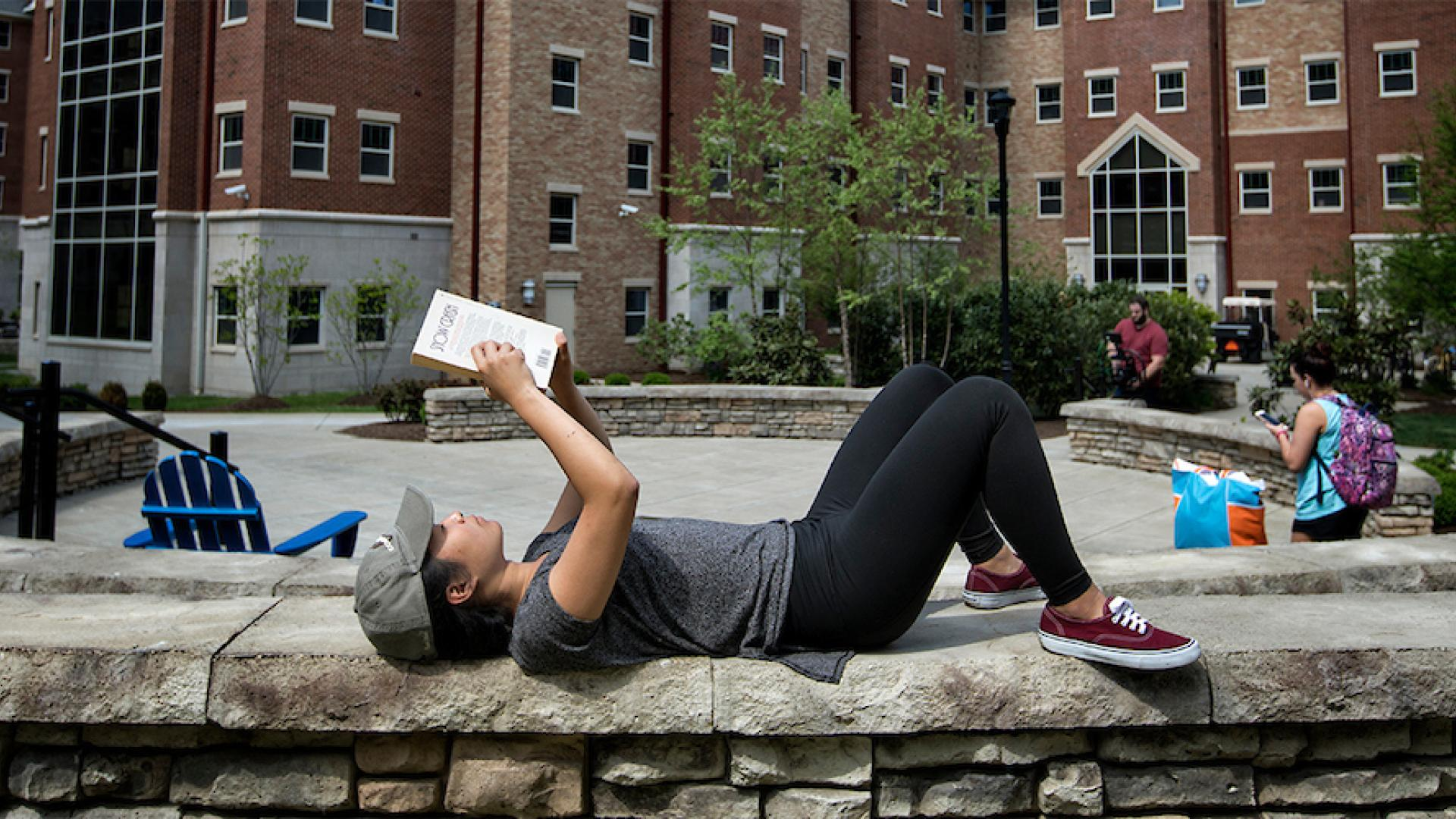 Student Enjoying a Good Book While Lying on a Stone Wall