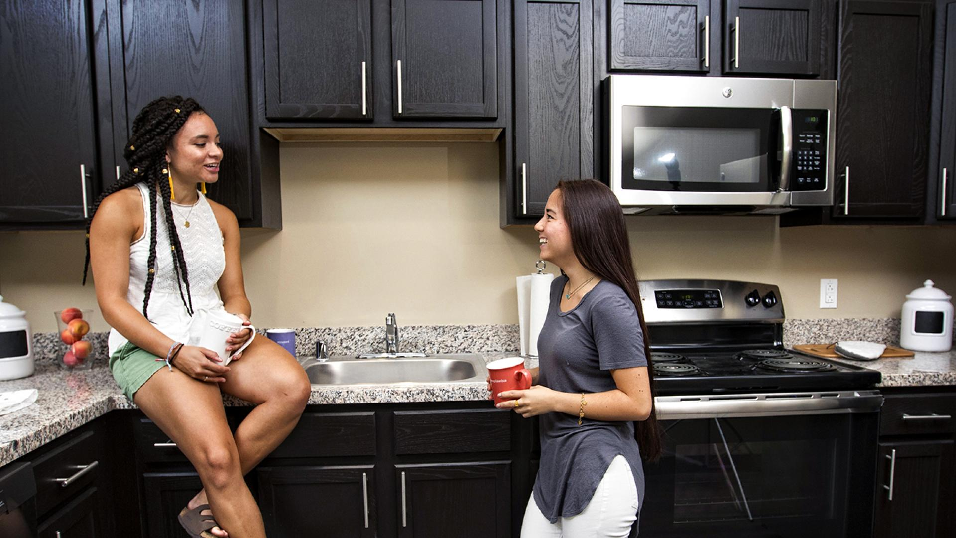 Female Students Talking in the Kitchen of a University Flats Condo
