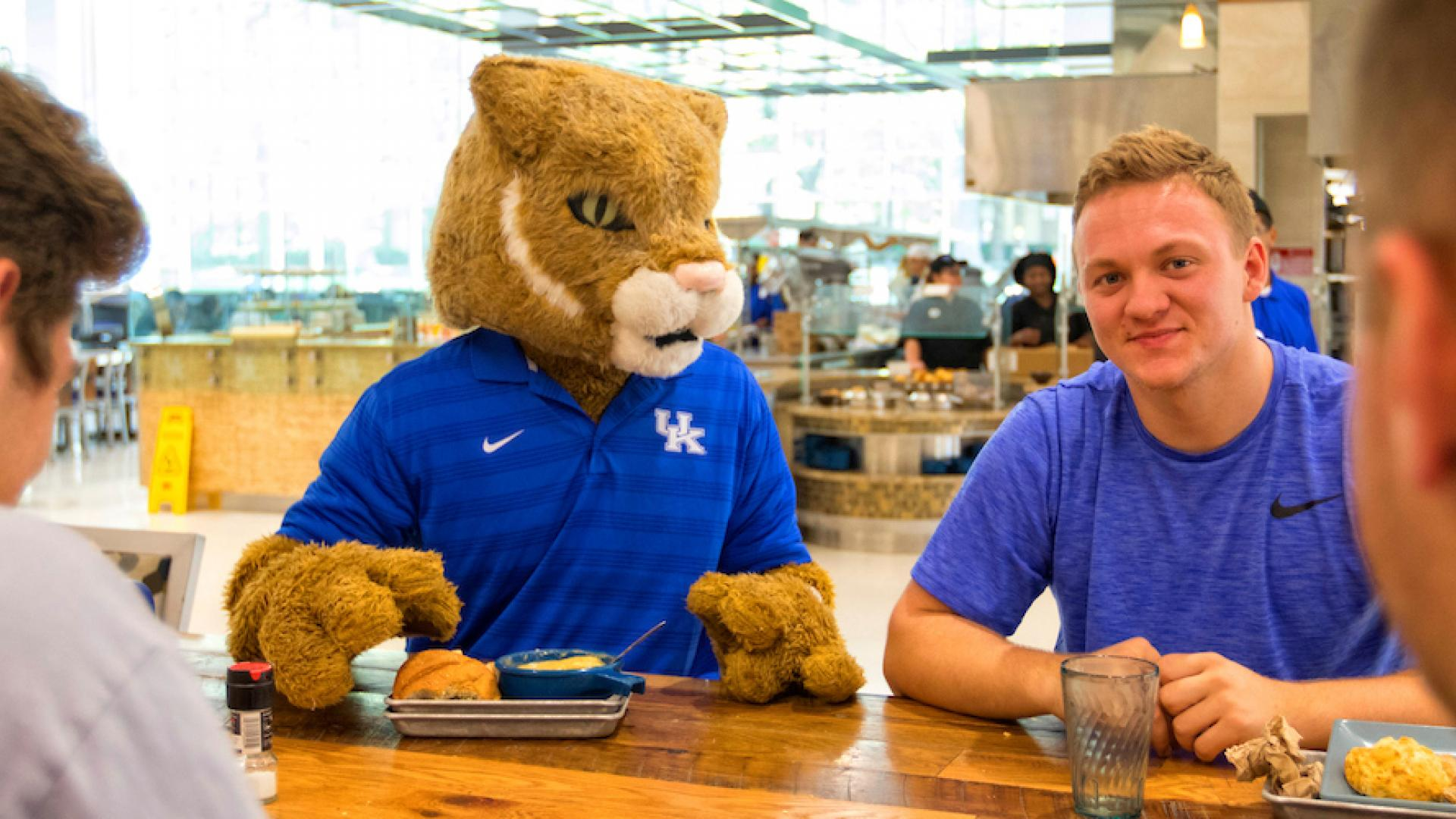 Students Enjoying the Comforts of UK Dining With the UK Wildcat Mascot