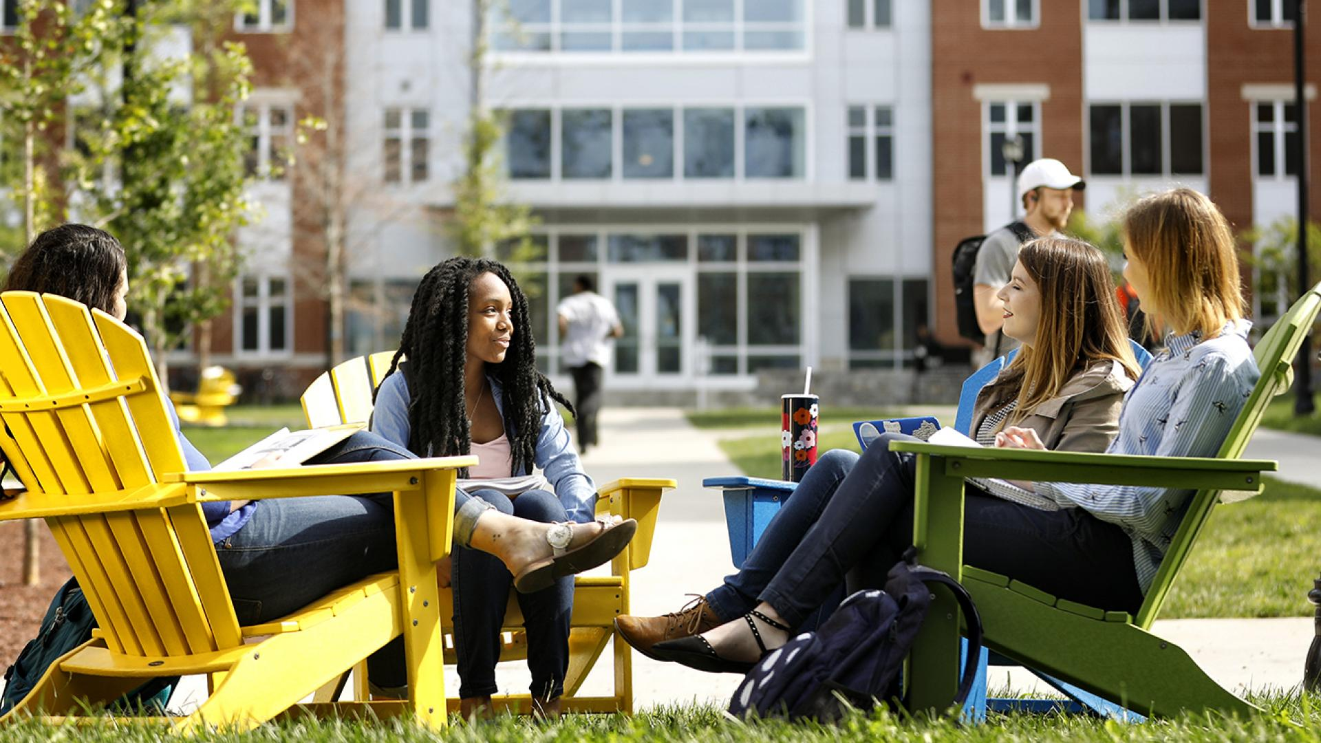 Female Students in Adorondick Chairs Enjoying a Sunny Day on a Residence Hall Lawn