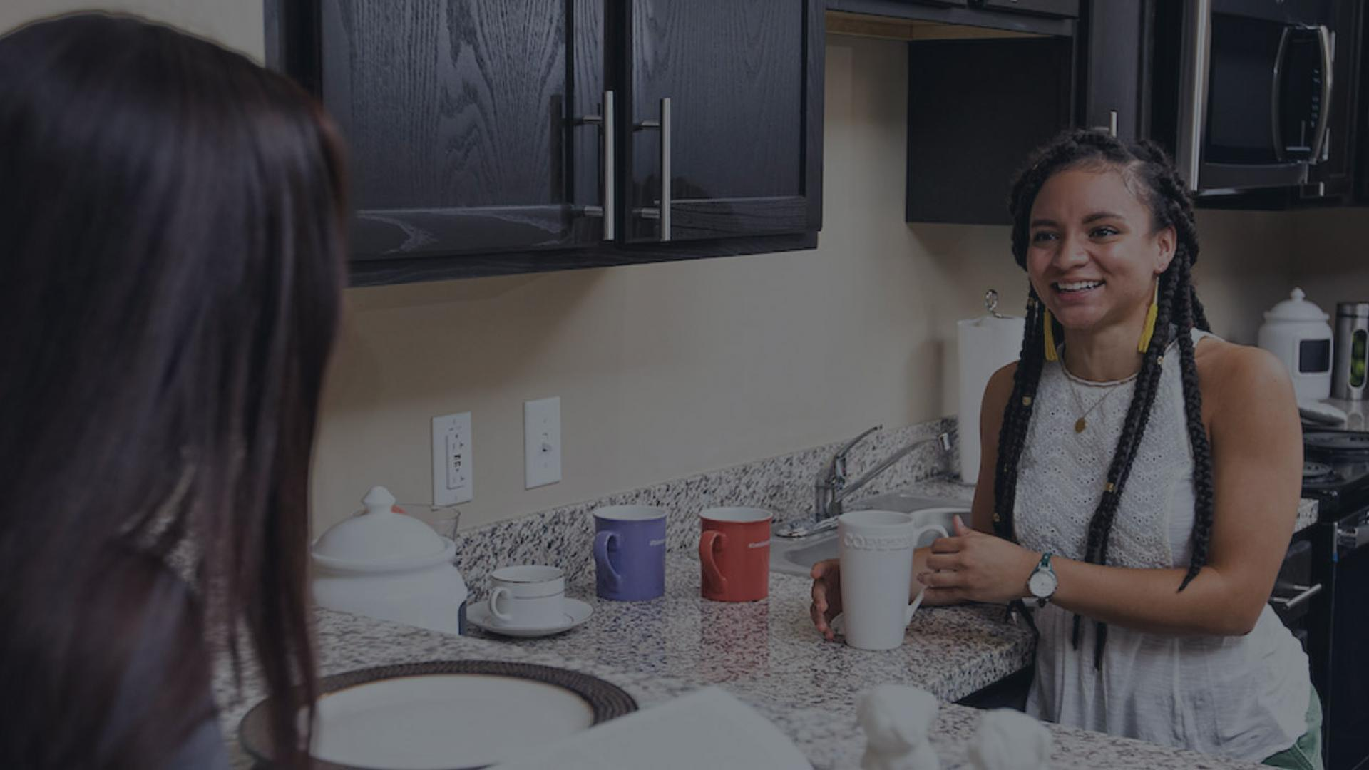 Two female students talking at the kitchen counter of their residence
