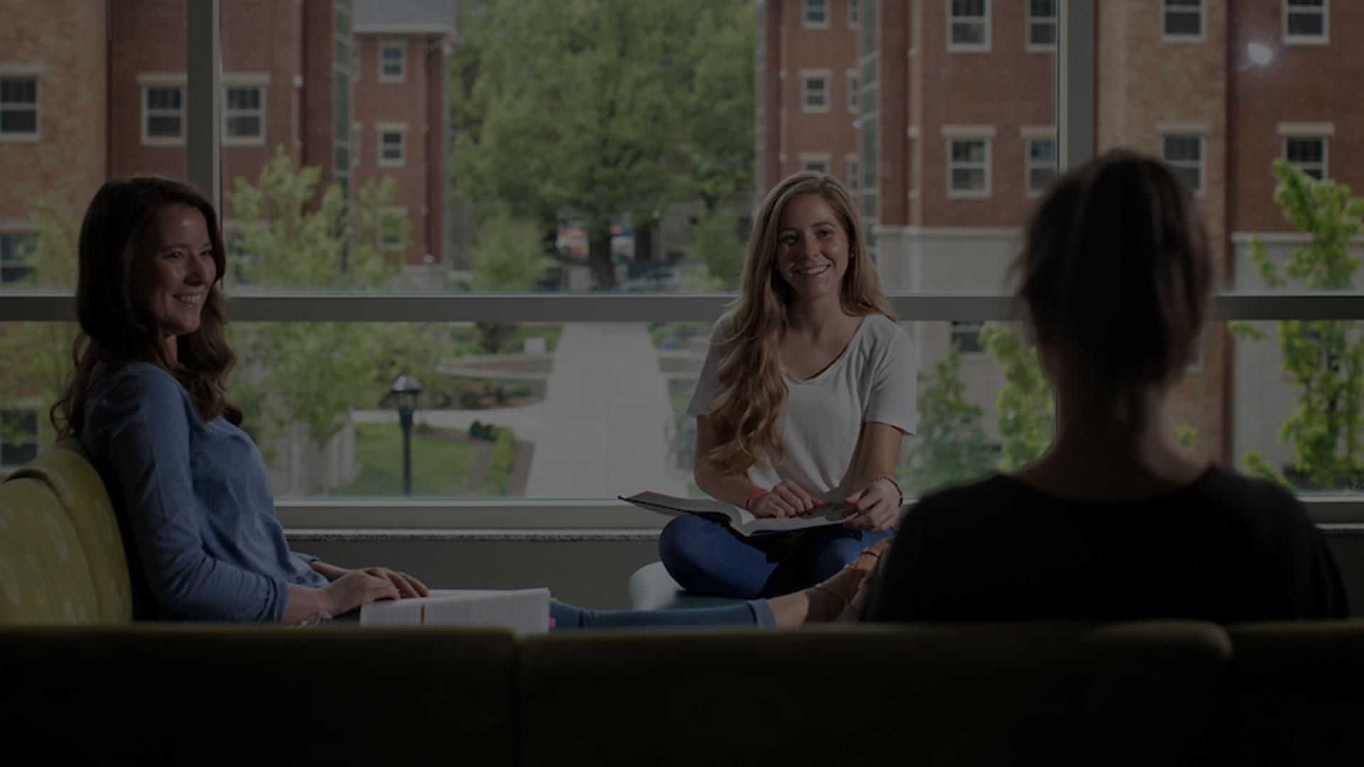 Three female students study together in the common area of a residence hall