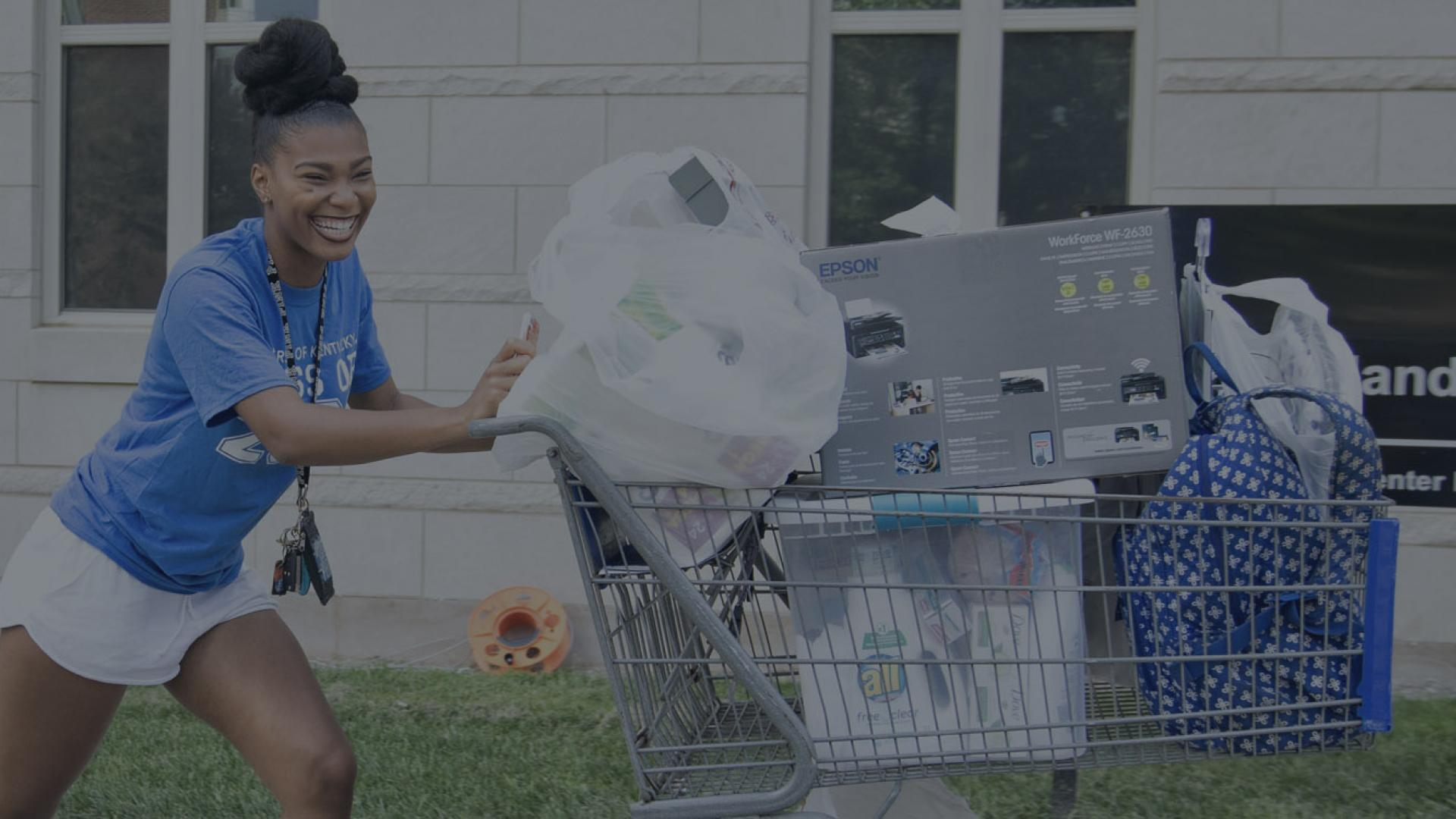 A female student gleefully pushes a loaded down shopping cart toward her new residence in Woodland Glen