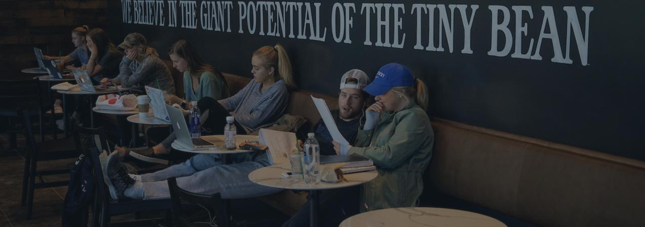 """Seven students sitting individually at round tables with their laptops open in a coffee shop with the words on the wall behind them in all caps """"WE BELIEVE IN THE GIANT POTENTIAL OF THE TINY BEAN"""""""