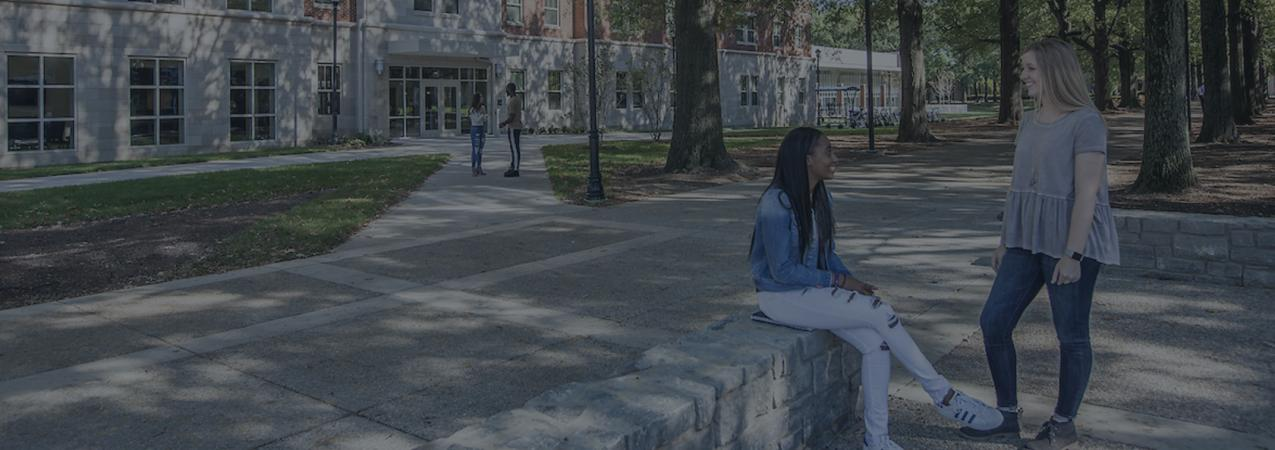 Two female students (one sitting on a short rock wall while the other stands) talking to each other in front of the new Lewis Honors College building