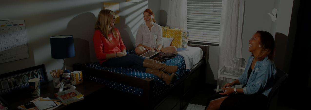 Three female students enjoy each others company in a residence hall room