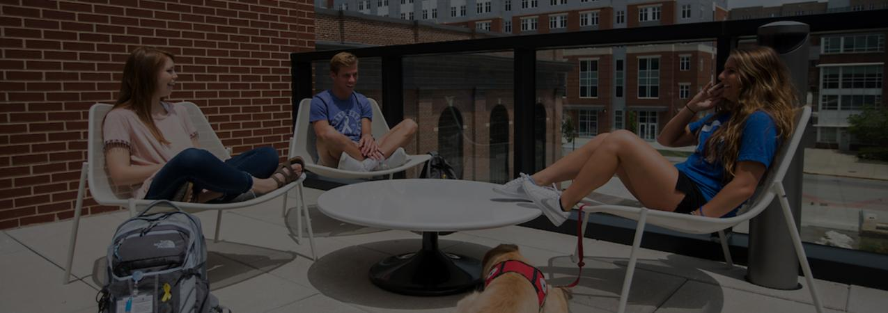 Two female (one with a training dog) and one maie student take the load off their feet on the upper deck patio of the new Student Center