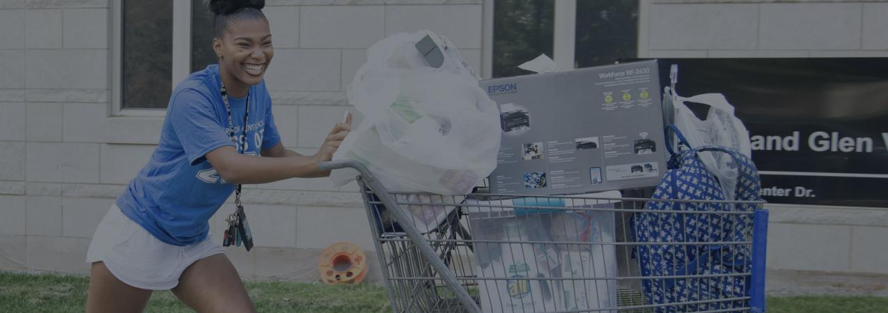 An eager volunteer female student pushes a cart with a partial load of someone's move-in material.