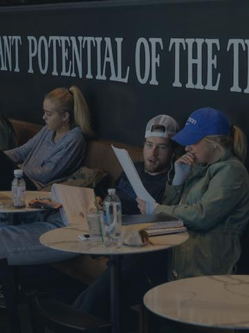 "Seven students sitting individually at round tables with their laptops open in a coffee shop with the words on the wall behind them in all caps ""WE BELIEVE IN THE GIANT POTENTIAL OF THE TINY BEAN"""