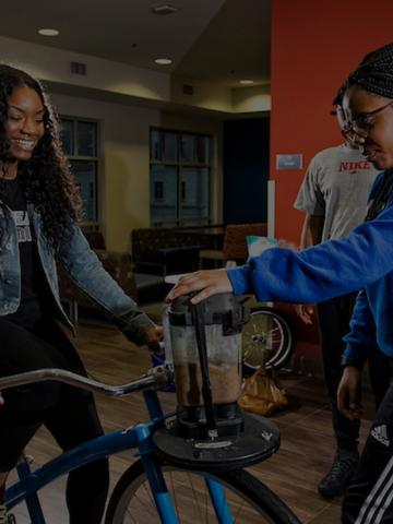 Two female students create a smoothie using pedal power