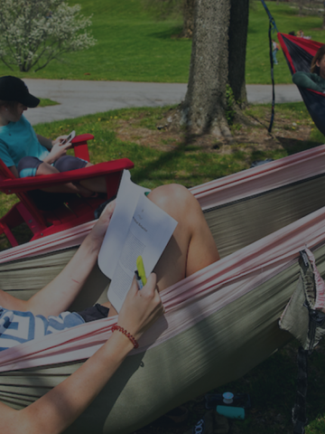 Three students reading while enjoying UK's sunny outdoors - two in hammocks and one in an Adirondack chair