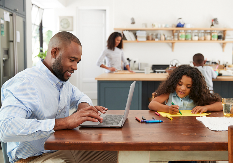Young black man working on laptop in the kitchen with family nearby working on different projects