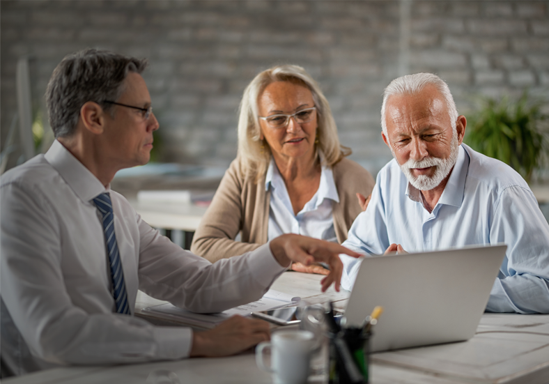 Husband and wife reviewing their retirement account together with the help of an adviser