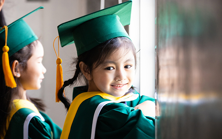 Girl in kindergarten graduation cap and gown