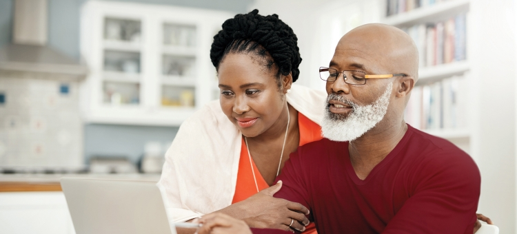 Happy older couple discussing insurance options.