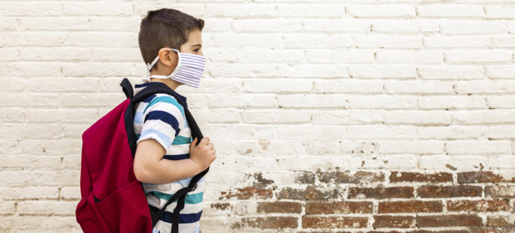 Child wearing mask and backpack