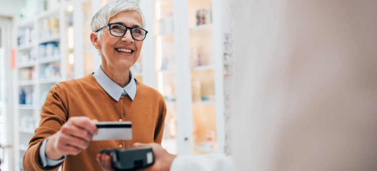 Woman using a flexible spending account card at pharmacy.