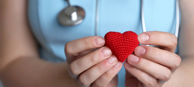 Health care provider holding crocheted heart.