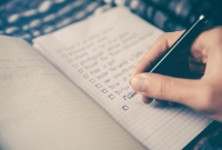 hand writing a list with checkboxes