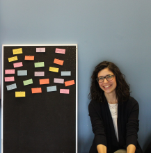 Picture of Tatiana sitting next to the compliment board where participants have pinned their compliments