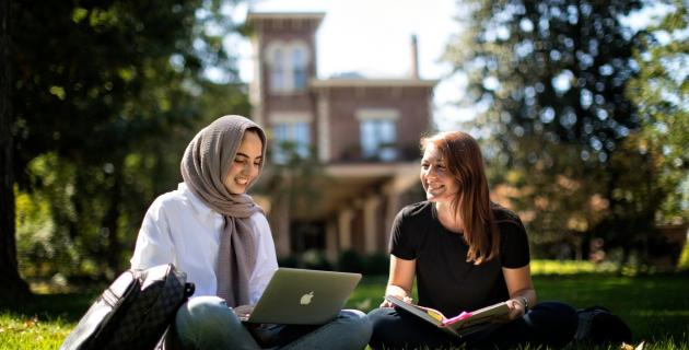 Two students outside with laptops
